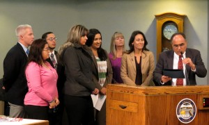 Yolo County Supervisor Jim Provenza presents a proclamation to a domestic violence survivor.