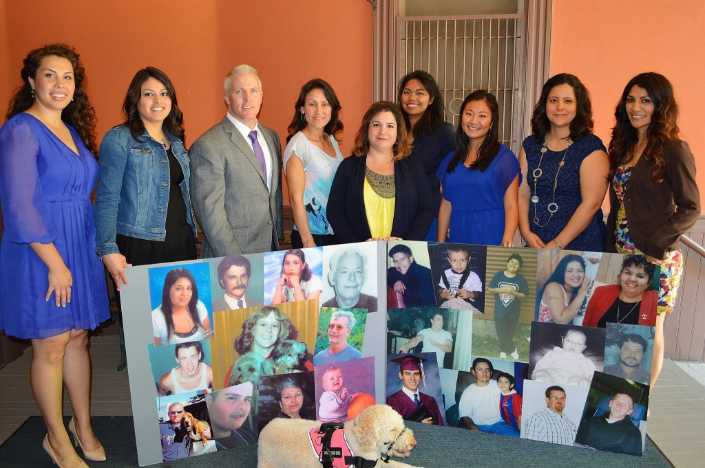 District Attorney Reisig with Victim Services Program representatives and photos of deceased crime victims