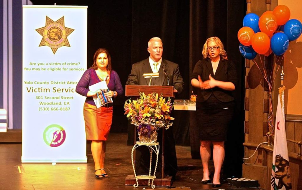 Photo from the 2016 Victim Tribute Ceremony, from left to right, Victim Advocate Program Coordinator Laura Valdes, District Attorney Jeff Reisig, & the Sign-Language Translator.