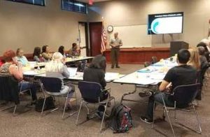 The image depicts Deputy District Attorney Chris Bulkeley at a recent Neighborhood Court training session.