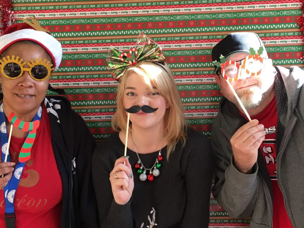 Image depicts previous Mental Health Court participants having fun at the photo booth.