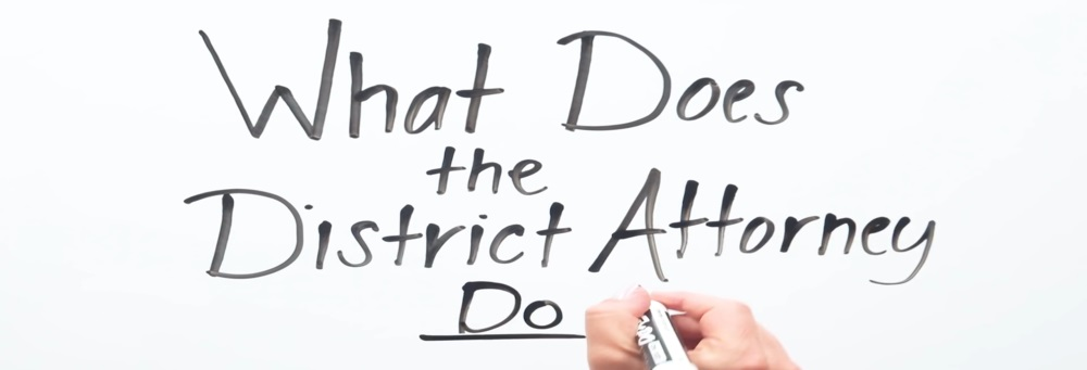 """Image of hand written text that says """"What Does the District Attorney Do?"""""""