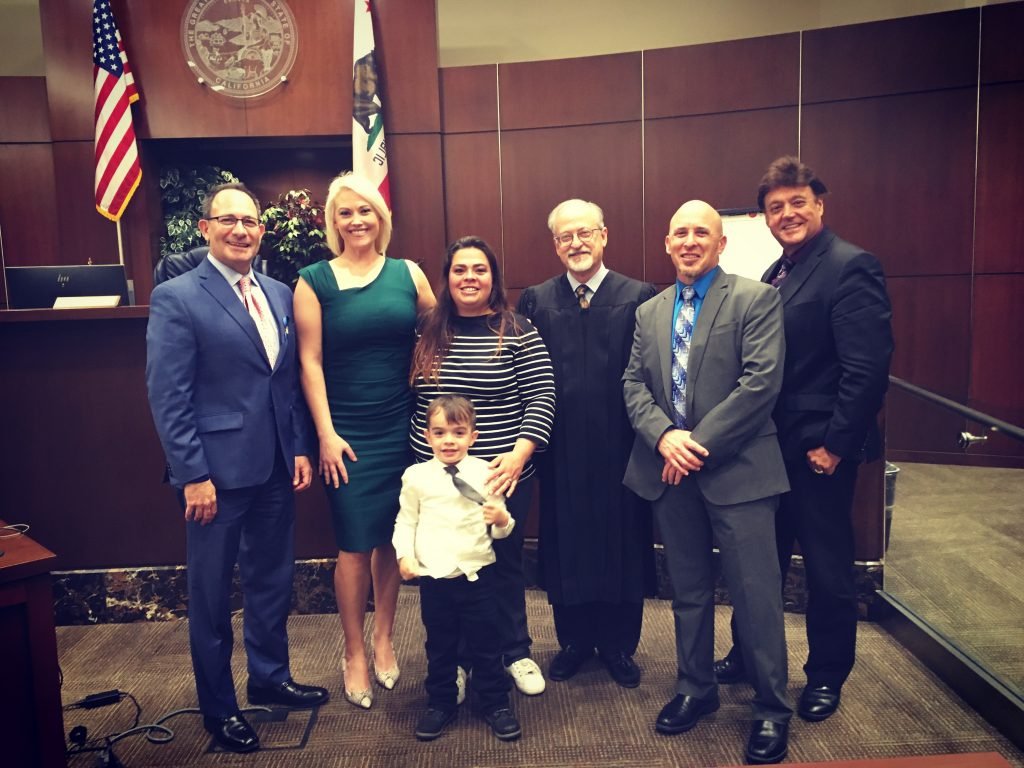 Image includes the addiction intervention court graduate along with her son and the AIC team.